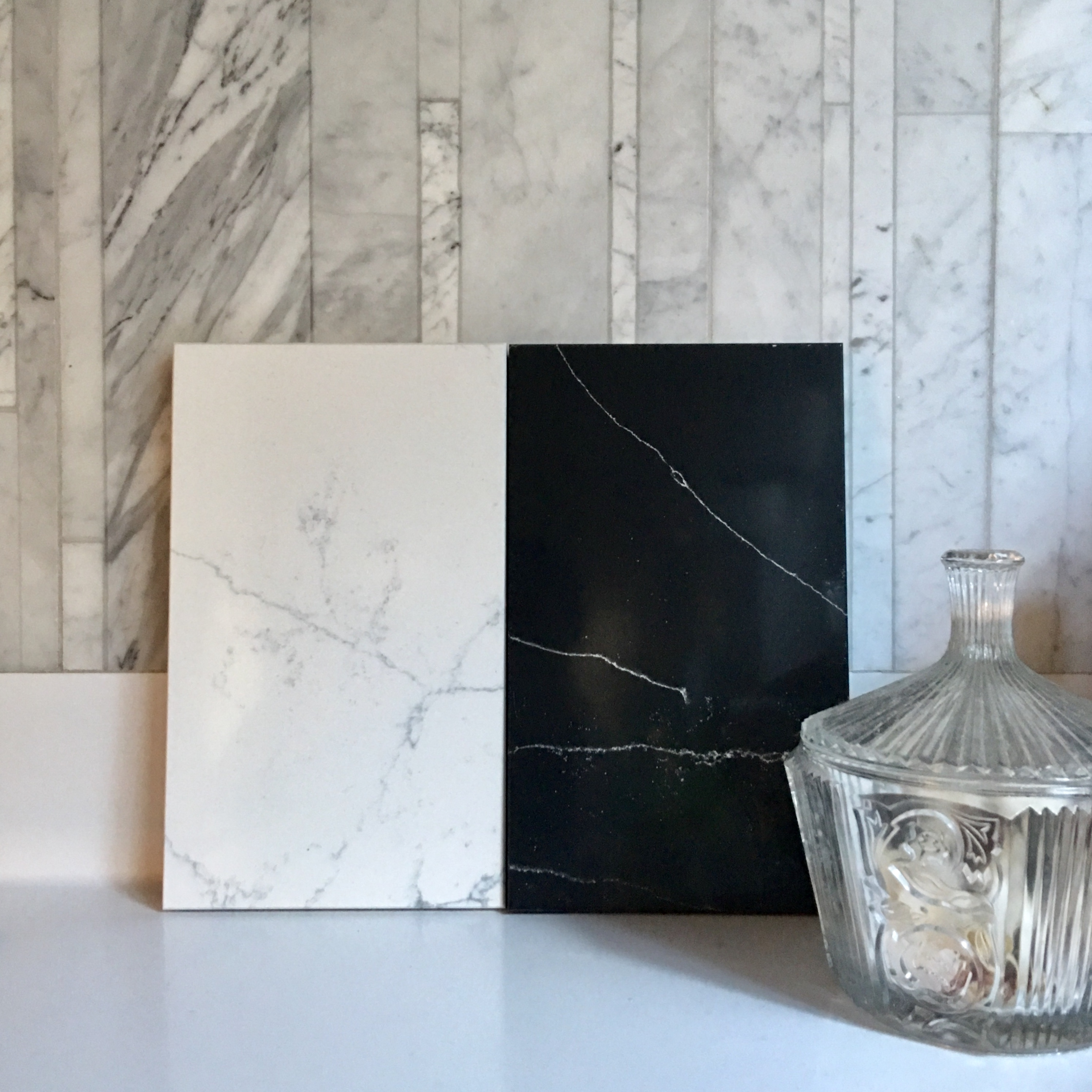 From the Compac 'Unique' collection of faux marble solid surfacing materials. Right: 'Unique Marquina' sample; Left 'Unique Venatino' sample, both shown against Salvatori Lithoverde marble.