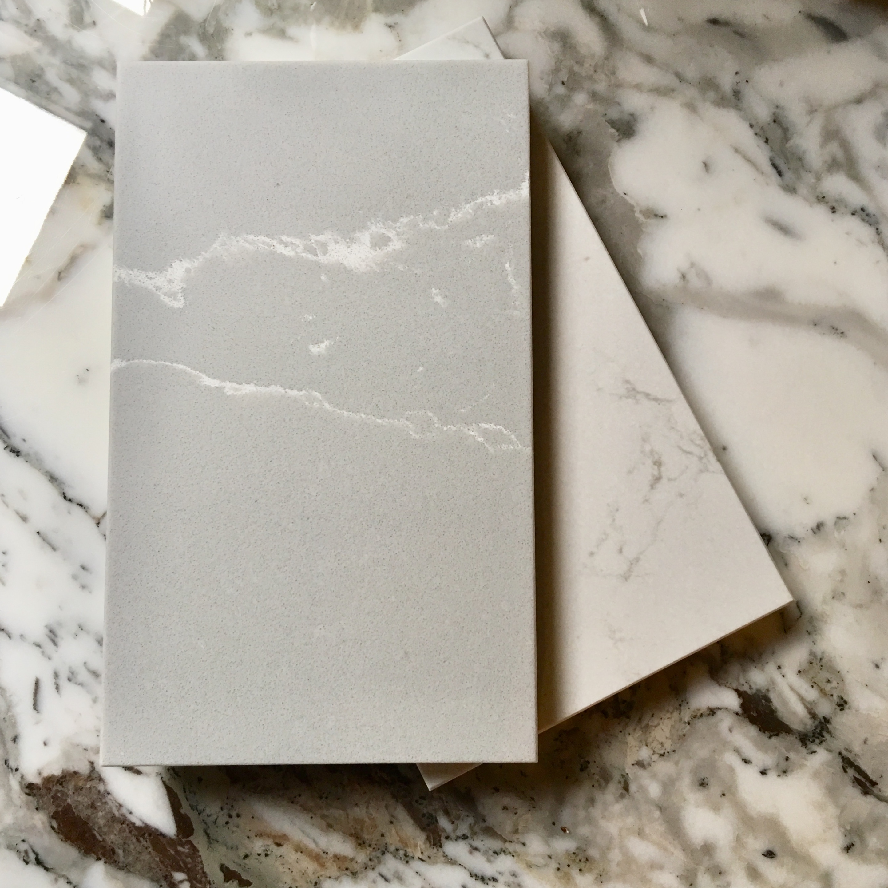 From the Compac 'Unique' collection of faux marble solid surfacing materials. Top: 'Unique Argento' sample, underneath 'Unique Arabescato' sample, both shown on top of a Knoll Saarinen table Arabescato marble top.